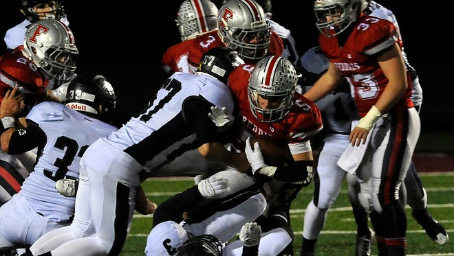Fredericktown running back Tyler Ohl is brought down by a host of Grandview heights defenders during a Division VI regional final against Grandview Heights on Saturday, Nov. 21, 2015, at White Field in Newark.