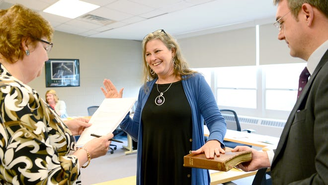 Joyce Brown is sworn in to the Asheville City School Board  by Paula Lovitt, left, and board attorney K. Dean Shatley, II, before a work session at the Asheville City School central office on Monday, April 3, 2017.