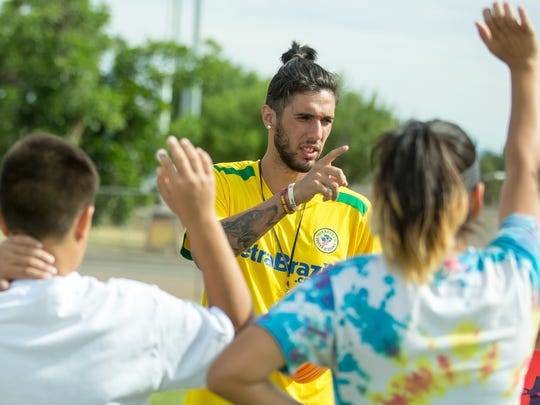 Challenger Sports British Soccer Camp coach Matheus Macedo, of Brazil, organizes a drill with teenage campers on Friday, June 2, 2017, at the High Noon Soccer Complex.