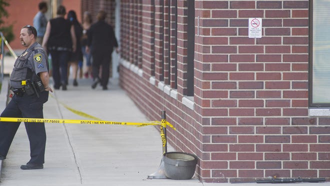 A rifle, seen at right, rests near where a DCF social worker Lara Sobel was shot and killed outside Barre City Place on Friday night.