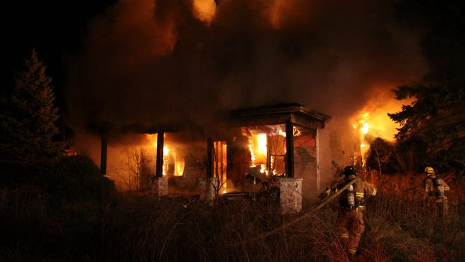 Firefighters work at the scene of a blaze Saturday in Howell Township.