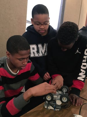 Christian Caldwell, Nicholas Brown and Antonio Taylor prepare their robot for a strength challenge Wednesday at NSU-RC1, a robotics competition at Northwestern State University in Natchitoches.