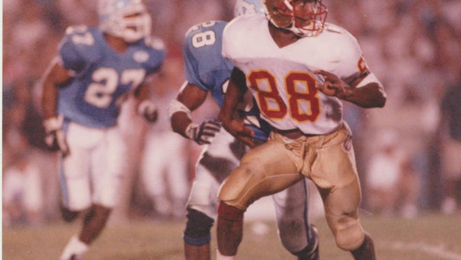 Florida State receiver Kez McCorvey races downfield and looks back towards quarterback Charlie Ward in the Seminoles' win at North Carolina in 1993.