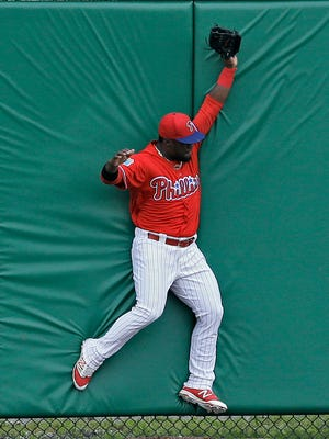 Phillies center fielder Odubel Herrera crashes into the wall after making the catch on a fly out by Toronto Blue Jays' Kevin Pillar during the first inning of a spring training baseball game Friday, March 25, 2016, in Clearwater, Fla. (AP Photo/Chris O'Meara)