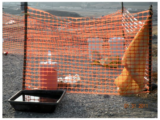 This photo depicts a worker decontamination area, which included a bucket of water, for 900 workers.