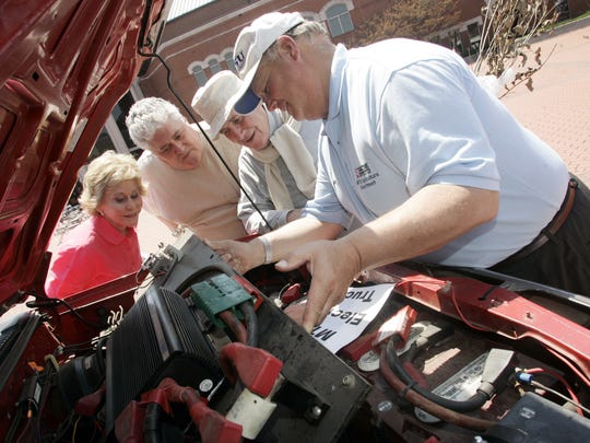 From left, Bobbie Duke, her son Patrick Duke and husband John Duke watch as MTSU professor Cliff Ricketts shows off the engine in an alternative-energy pickup truck that is powered by batteries during Earth Day activities on the Civic Plaza in Murfreesboro on April 21, 2007.