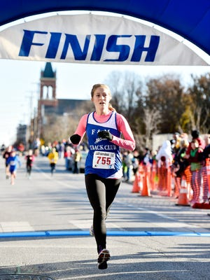 Julia Zielinski, a Northeastern alumna currently living in Oklahoma City, crosses the finish line as the first female finisher of the YMCA of York and York County's 21st annual Turkey Trot 5K race Thursday, Nov. 23, 2017, in York. Zielinski said she was hit by a car while running in mid-September and, due to an injury in her right leg, did not expect to finish as the first woman. More than 5,100 participants were expected to hit the streets on Thanksgiving morning.