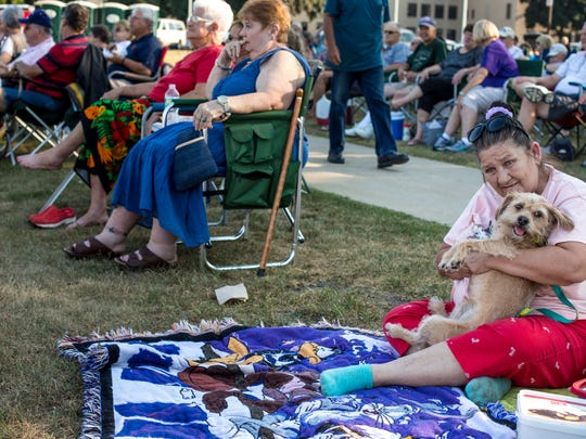 "Linda McCarty, of Port Huron, watches the band with her dog, ""Baby Dog,"" during Rockin' the Rivers Thursday, August 4, 2016 at Kiefer Park in Port Huron."