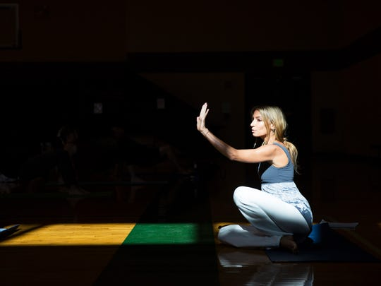 """Wendy Campbell, 41, leads a yoga class at the North Collier Regional Park gym on Friday, Dec. 16, 2016. Campbell, who was diagnosed with hodgkin's lymphona 10 years ago, is trying to bridge that gap between cancer treatment and mental well-being through her start-up organization called """"Survive & Thrive."""" Campbell teaches cancer survivor yoga and provides them with other wellness resources."""
