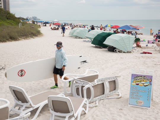 Sean Hanley, a full-time employee of Cabana Dan's beach rental service, retrieves paddle boards and lounge chairs at the end of the day at Vanderbilt Beach on Wednesday, April 19, 2017, in North Naples. The company closes its Barefoot Beach location during the summer months due to a dip in beach traffic.