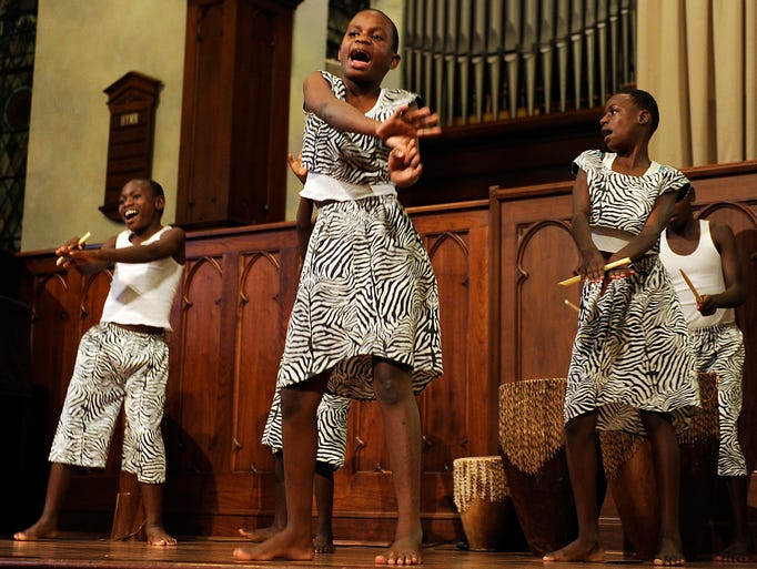 Richard Sebuliba, Lukia Logose, and Brender Nasaazi of the Ugandan Kids Choir perform the Oseke Dance during a performance on Wednesday, Aug. 20, 2014, at the Second Presbyterian Church. The dance, from the Northern part of Uganga, gets its name from a flute traditionally played by shepherd while their cattle grazes. The Uganda Kids Choir is a ministry of Childcare Worldwide, a non-profit child-sponsorship organization.