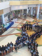 Attendees at the first Child Abuse Awareness Day at Nemours/A.I. DuPont Children's Hospital form a blue ribbon in the hospital lobby. The blue ribbon was adopted as a symbol by child abuse prevention groups.