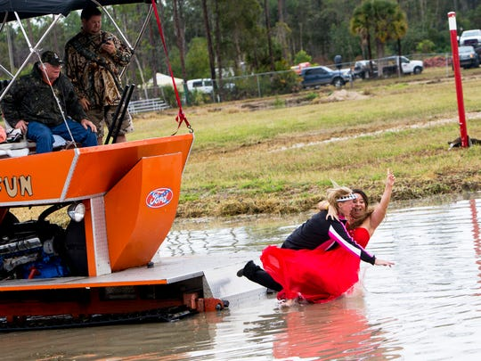 2016-2017 Swamp Buggy Queen Erica Marie Flesher, 21, from right, throws her hand in the air as Big Feature winner Bonnie Walsh, 57, jumps with her into the sippee hole during the Budweiser Winter Classic swamp buggy races at Florida Sports Park in Naples, Florida on Sunday, Jan.  29, 2017.