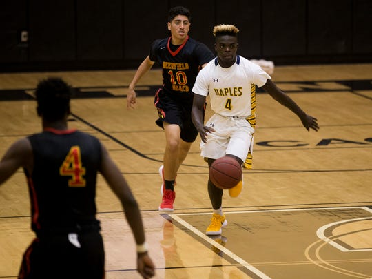 Naples' Wooby Theork (4) brings the ball up the court against Deerfield Beach in a first round game of the Gulfshore Holiday Hoopfest at Golden Gate High School Wednesday, Dec. 27, 2017 in Golden Gate Estates.