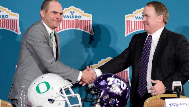 Oregon head coach Mark Helfrich, left, and TCU head coach Gary Patterson, right, shake hands following a news conference for the Alamo Bowl NCAA college football game, Friday, Jan. 1, 2016, in San Antonio. The two teams meet on Saturday.