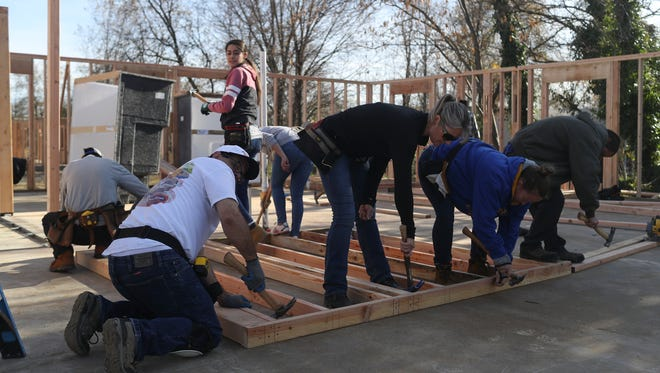 In this 2017 file photo, Roxi Mueller, center, works with neighbors as part of the Community Housing Improvement Program.