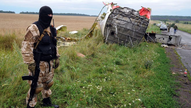 An armed, pro-Russia militant stands guard at the site of the crash of  Malaysian Airlines Flight MH17.