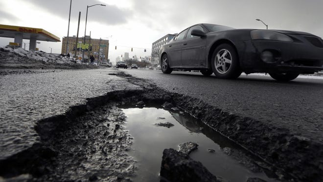 In this Feb. 11, 2014, photo, a car drives by a pothole in Detroit.