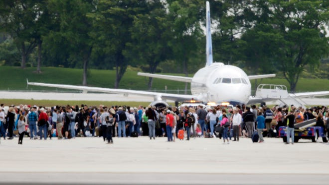 People stand on the tarmac at the Fort Lauderdale-Hollywood International Airport after a shooter opened fire inside the terminal, Friday, Jan. 6, 2017, in Fort Lauderdale, Fla.  A gunman opened fire at the Fort Lauderdale airport Friday, killing several people and wounding others before being taken into custody, officials said.