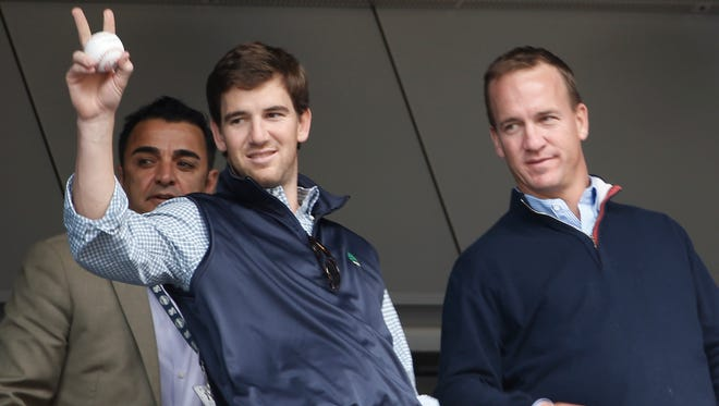 Giants quarterback Eli Manning, left, stands beside his brother, Denver Broncos quarterback Peyton Manning, as they watch the Yankees play Tampa Bay on Sunday.