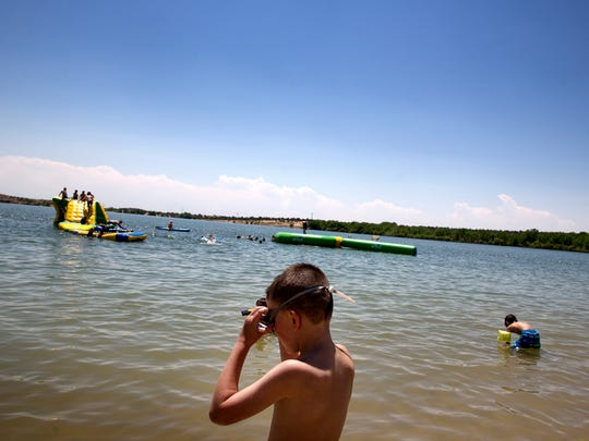 Tate Macsalka adjusts his swimming goggles Monday before taking a swim at Farmington Lake.