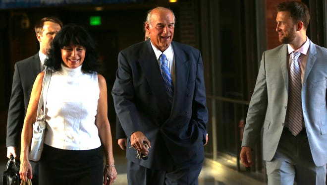 """Former Minnesota Gov. Jesse Ventura, center, arrives at court with his wife, Terry, and others for his defamation lawsuit against """"American Sniper"""" author Chris Kyle in St. Paul, Minn on July 22, 2014. Kyle wrote in his best-seller that he decked Ventura in a California bar in 2006 after Ventura allegedly said Navy SEALs """"deserve to lose a few."""""""
