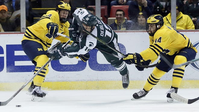 Michigan State's Matt DeBlouw (19) gets knocked over by Michigan's Cutler Martin (4) while Michigan's Tyler Motte (14) helps defend during the first period of a college hockey game at Joe Louis Arena on Friday, Feb. 5, 2016, in Detroit. (AP Photo/Duane Burleson)