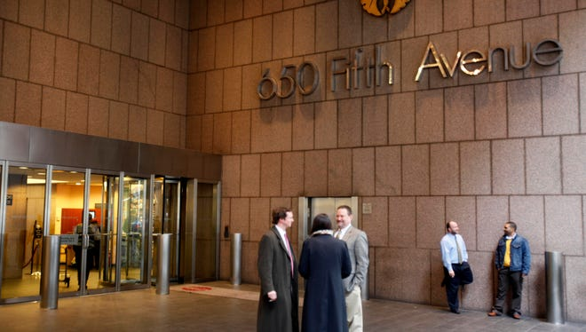 People stand near an entrance to 650 Fifth Ave. in New York.