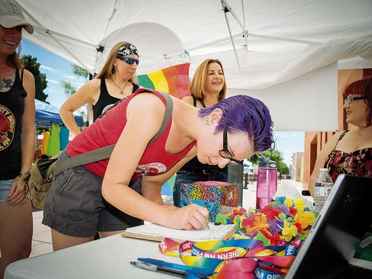 Sophia Bailey signs up for an email newsletter at the Farmers and Crafts Market while visiting the Southern New Mexico Pride booth. The booth was set up to help spread the word about Pride Week, a series of events this week, organized by Pride to promote tolerance and unity between the LGBTQ community and others in southern New Mexico.