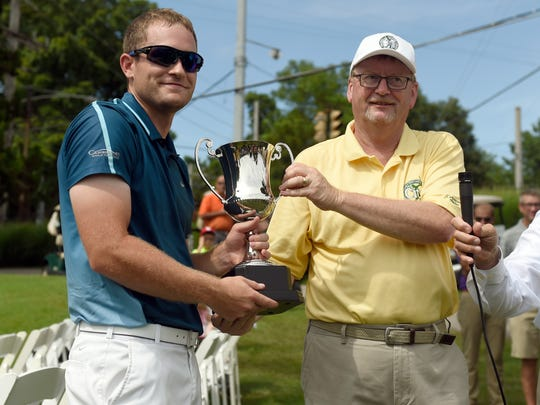 Logan Osborne (left) accepts the Evansville Courier & Press City Tournament Champion trophy from Tim Ethridge after finishing at 4-under par at Evansville Country Club in Evansville Sunday.