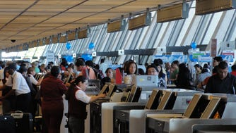 Airline passengers line up at the ticket counters to check-in for flights at Washington Dulles International Airport on July 26, 2011.