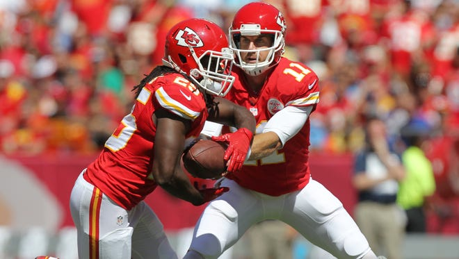 Kansas City Chiefs quarterback Alex Smith (11) hands off the ball to running back Jamaal Charles (25) in the first half against the Tennessee Titans on Sunday.
