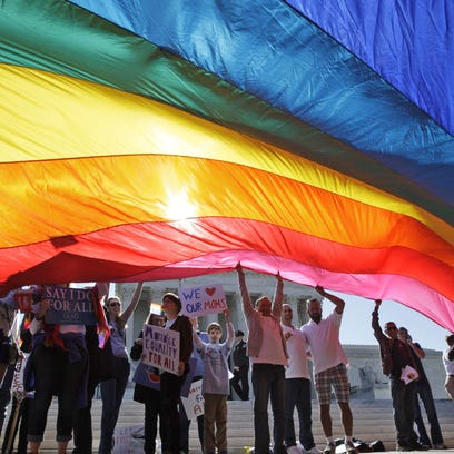 Gay marriage supporters wave a huge flag in front of