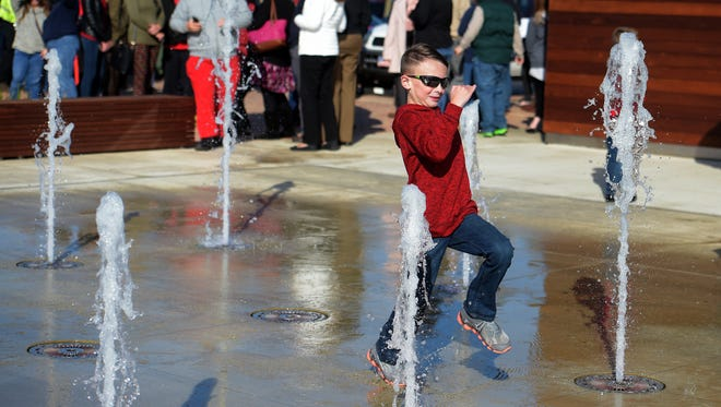 Maxon Elstro, 8, takes a chance running through the fountain Friday, Oct. 28, 2016 during the official opening of the Jack Elstro Plaza in downtown Richmond.