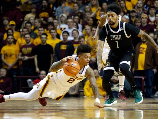 South Carolina Upstate's Mike Cunningham, right, watches as Minnesota's Nate Mason controls the ball as he falls during the first half of an NCAA college basketball game Friday, Nov. 10, 2017 in Minneapolis. (AP Photo/Jim Mone)