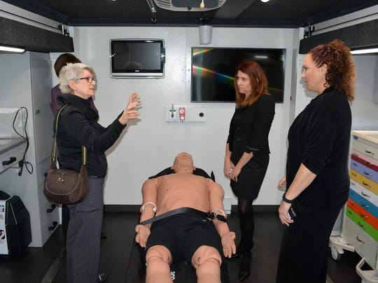 Jennie Nemec, left, asks a question to Heidi Schultz, front right, of the Helmsley Charitable Trust while touring inside one of the Simulation in Motion trucks.