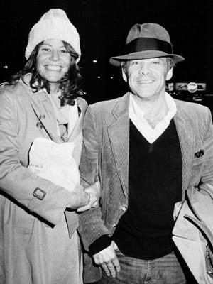 """FILE - In this Nov. 28, 1980 file photo, Chuck Barris, host of the television's """"Gong Show,"""" and Robin Altman leave the Pierre Hotel in New York. Game show impresario Barris has died at 87. Barris, the madcap producer of """"The Gong Show"""" and """"The Dating Game,"""" died of natural causes Tuesday afternoon, March 21, 2017, at his home in Palisades, New York."""