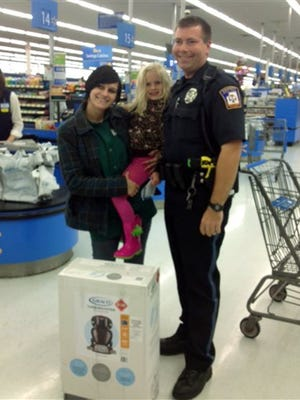 This photo provided by Walmart shows Emmett Township, Mich., Department of Public Safety Officer Ben Hall, right, with Alexis DeLorenzo, her daughter and the child's seat he purchased for them. Hall was on patrol Friday in the southern Michigan community when he pulled over DeLorenzo's vehicle after someone reported that it had an unsecured young child inside. DeLorenzo said she knew that they could have been ticketed, but instead, Hall told her to meet him at a Wal-Mart, where he bought her the seat.