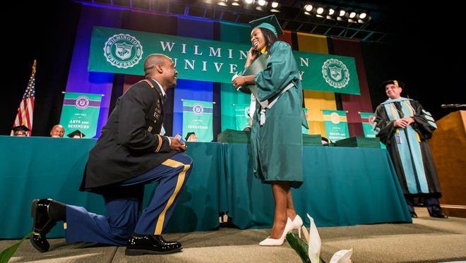 Second Lt. Artist Jones proposes to his girlfriend Loveleigh Goode after surprising her with an early homecoming from his deployment to Germany during graduation ceremonies for Wilmington University at the Chase Center on the Riverfront in Wilmington on Sunday afternoon.