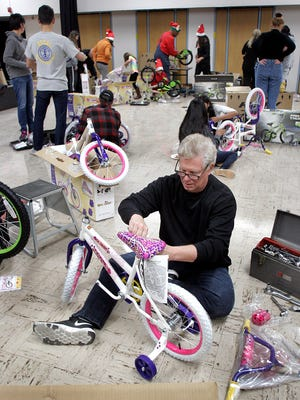 William Klepper puts a bike together during the Holiday Children's Bike Assembly Party at Monte Vista School in Simi Valley last week. Every year, three Rotary clubs in Simi Valley put on the event so volunteers can come together to assemble 250 bikes for underprivileged children. The bikes go to area churches and youth organizations, which will give them out closer to Christmas.