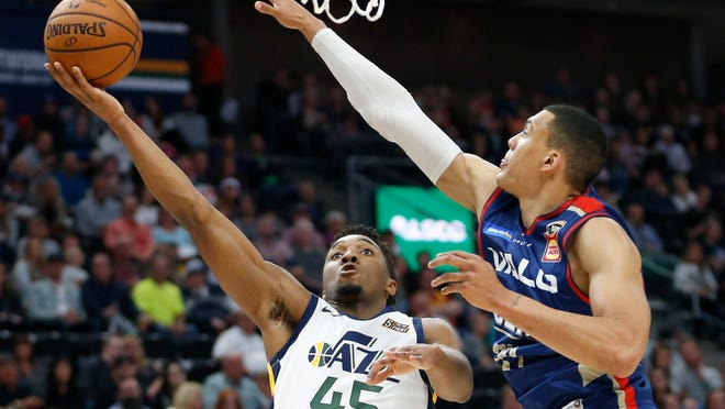 Utah Jazz guard Donovan Mitchell (45) lays the ball up as Adelaide 36ers forward Jake Wiley, right, defends during an NBA exhibition game Oct. 5, 2018, in Salt Lake City.
