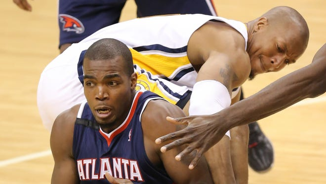 Atlanta Hawks forward Paul Millsap and Pacers forward David West battle for a loose ball in the second half of Game 2 Eastern Conference playoffs against the Atlanta Hawks at Bankers Life Fieldhouse on Tuesday, April 22, 2014. The Pacers won 101-85.