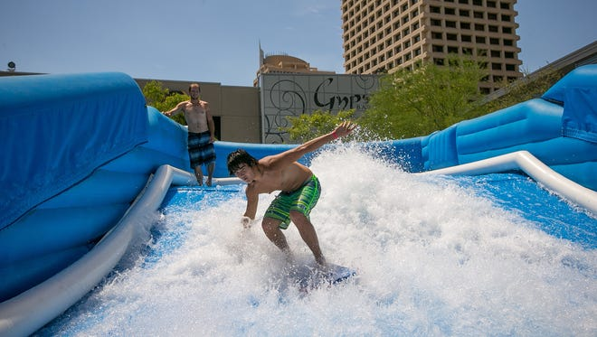 Jesse Baba, 18, stands up on a bodyboard on the FlowRider wave simulator at CityScape's Patriot Square as part of the Surfing on Central event in Phoenix on Thursday, July 10, 2014.