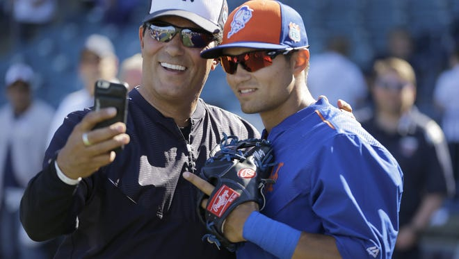 New York Yankees coach Lee Mazilli, left, takes a photo with his son, New York Mets infielder L.J. Mazilli, before a spring training baseball game Tuesday in Tampa, Fla. Yankees fans who have Comcast will not be able to see the Yankees on the YES Network this season.