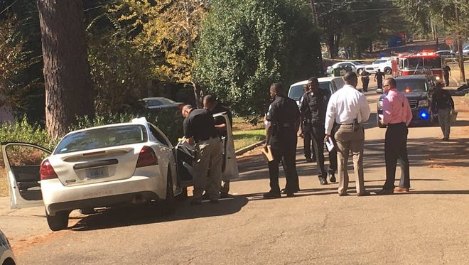 Police process a Grand Prix where a woman was shot dead on Thursday.