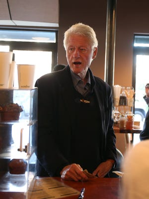 President Bill Clinton orders a decaf coffee on Saturday, Nov. 1, 2014, during a surprise stop to Stomping Grounds coffee shop in Ames, Iowa.