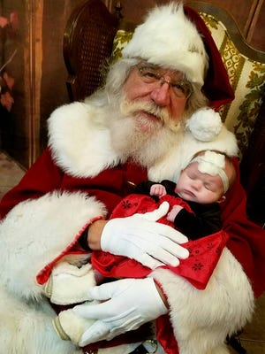 Santa Claus with a tiny  visitor at Mr. Mike's Grill.