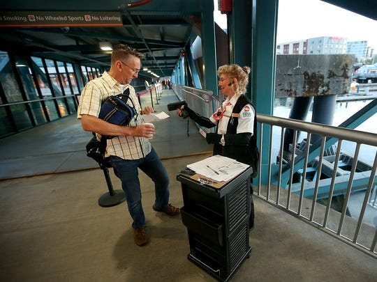 Kitsap Transit's Marie Pavlovich (right) scans the ticket passenger Bill Berko, of Bremerton, as he heads for the first sailing of the Rich Passage 1 to Seattle early Monday.