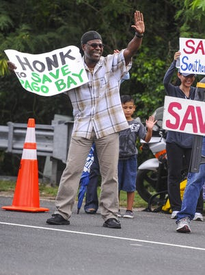 Members of the nonprofit group Save Southern Guam Inc. and other supporters greet passing motorists during a wave near the Pago Bay bridge in June 2016.
