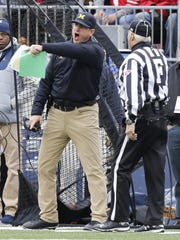 Michigan coach Jim Harbaugh, left, yells at the field judge during the first half Saturday at Ohio State.